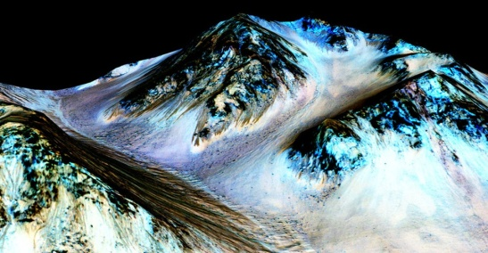 Dark, narrow streaks on martian slopes such as these at Hale Crater are inferred to be formed by seasonal flow of water on contemporary Mars. The streaks are roughly the length of a football field - from ASTRONOMY.COM