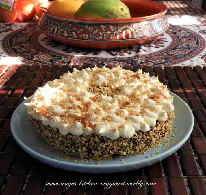 a chocolate cake. Covered in chocolate ganache and topped with a vanilla icing. Around covered with roasted peanut bits and finished with some caramel sauce